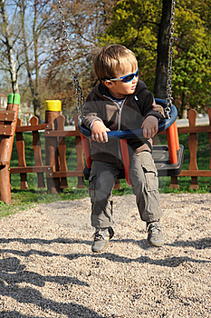 Boy With Sunglasses On Swing Stock Image - Image: 19199891