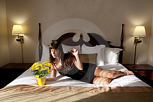 Beautiful Woman On Hotel Bed With Flowers Royalty Free Stock Image - Image: 19289856