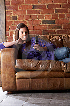 Young Woman With Phone On Sofa Stock Photography - Image: 19422652