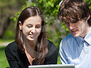 Couple Sitting In Park And Using Laptop Stock Photography - Image: 19519642