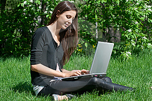 Young Woman Sitting In Park And Using Laptop Royalty Free Stock Photography - Image: 19528757
