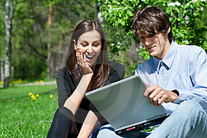 Couple Sitting In Park And Using Laptop Royalty Free Stock Photography - Image: 19539787