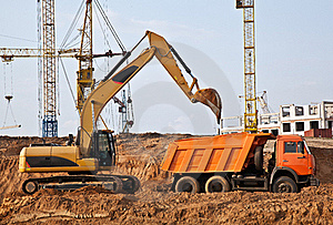 Backhoe Loading A Dump Truck Royalty Free Stock Images - Image: 19556419