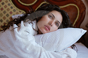 Beautiful Woman Lying On A Bed In A White Bathrobe Royalty Free Stock Photo - Image: 19649925