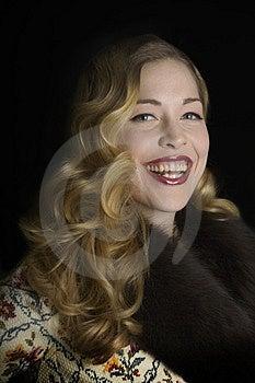 毛皮抓住衣领口的夹克的微笑的妇女 库存图片