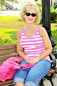 Adult Woman Siting On A Park Bench With Pink Purse Royalty Free Stock Images - Image: 20056479