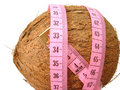 Coconut with pink tape measure over white background (concept of