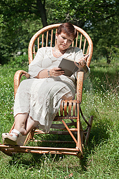 Mature Woman Reading Book In Rocking Chair Stock Photo - Image: 20530120