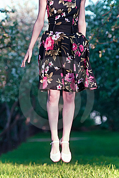 Girl In A Dress Jumps On A Green Lawn Royalty Free Stock Photos - Image: 20654898