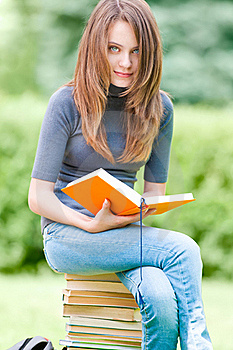 Happy Student Girl Sitting On Pile Of Books Stock Photos - Image: 20733993