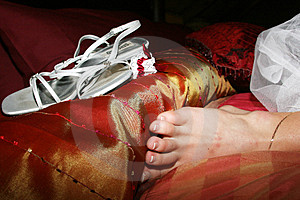Bride's feet next to her wedding shoe Royalty Free Stock Photo