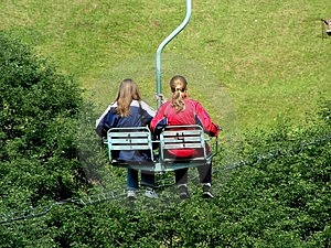 Two girls on a chair-lift in summer. Royalty Free Stock Image