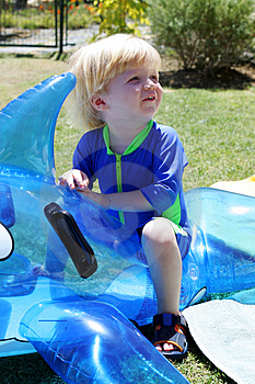Young Boy Or Child Sitting On Inflatable Dolphin By Swimming Pool Free Stock Photo