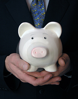 Businessman holding a piggy bank Royalty Free Stock Images