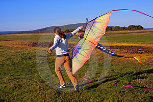 Young girl running with kite