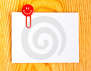 Close up of a  red paper clip and white paper