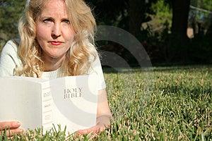 Scatto di una donna a leggere la sacra bibbia in erba alla ricerca.