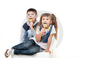 Little Brother And Sister Eating Tasty Candies Royalty Free Stock Photo - Image: 22239555