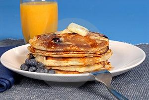 Una pila di blueberry pancakes con sciroppo d'acero e succo d'arancia.