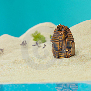Egyptian Bust In Miniature Sandy Landscape Stock Image - Image: 22986901