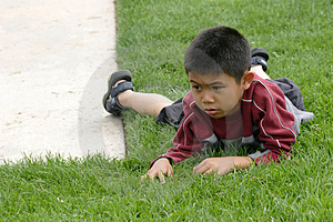 Boy Resting On The Grass Free Stock Photography