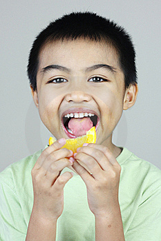 Boy Eating Orange Slice Stock Images - Image: 23093894