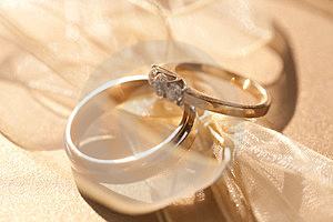 Two Gold Wedding Rings With Tender Ribbon Around Royalty Free Stock Images - Image: 23623149