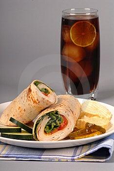 Un tacchino e formaggio svizzero avvolgere con sottaceti e patatine.