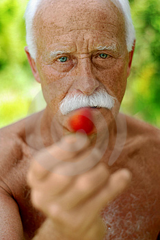 Senior with a strawberry Royalty Free Stock Images