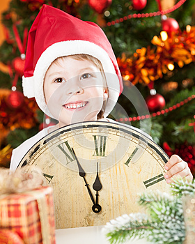 Kid In Santa`s Hat Holding Vintage Clock Royalty Free Stock Photos - Image: 25860958