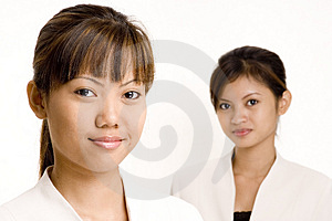 Dos sonrientes de las mujeres asiáticas en trajes de negocios sobre fondo blanco.