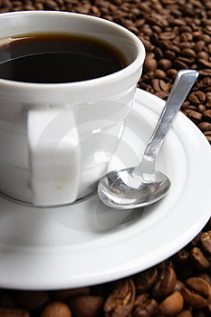 Cup with coffee, costing on coffee grain Stock Photography