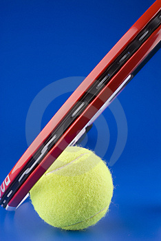 Tennis ball is next to a part of a tennis racket
