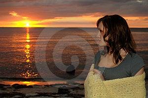Женщина обернутая в одеяле на заходе солнца Стоковое Изображение RF - изображение: 3983016