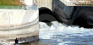 Fishing the Powerful Dam Outlet Royalty Free Stock Photo