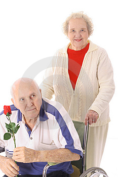 Wife pushing elderly husband Stock Image