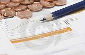 Coins, pencil and stock market graph Royalty Free Stock Image
