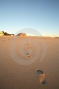 A piedi nudi stampa sulla spiaggia che conduce a un lontano casa al mare in questo luogo di vacanza di immagine.