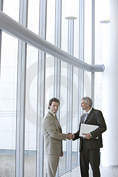 Shaking hands in front of windows Stock Image