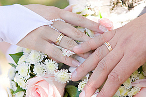 Two hands with wedding rings on the flower bouquet