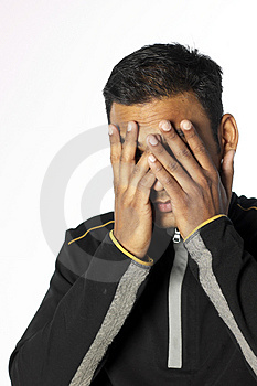 Young man with hands over  his face Stock Image