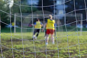 Soccer players in front of net Stock Image