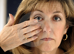 Woman Inserting Contact Lens in Eye Stock Image