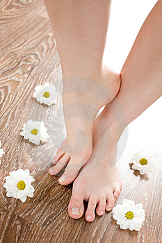 Female feet on the dark floorboard Royalty Free Stock Image