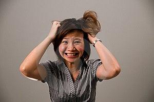 Asian lady in abbigliamento di affari, sento molto frustrato, strappandosi i capelli.