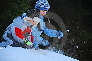 Siblings playing in snow Stock Photography