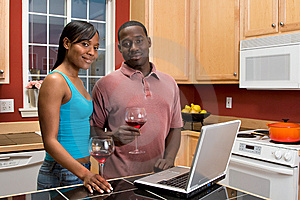 African American Couple Using Laptop in Kitchen Free Stock Photos