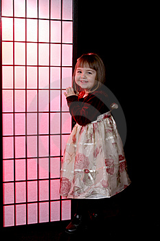 Pretty Little Girl Standing Next To A Pink Screen Royalty Free Stock Photo - Image: 5479925