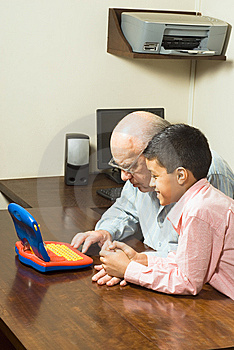 Grandfather and Grandson Looking at a Toy Computer Free Stock Photography