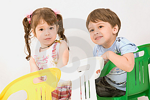 Adorable children sitting on colorful  chairs Free Stock Photography